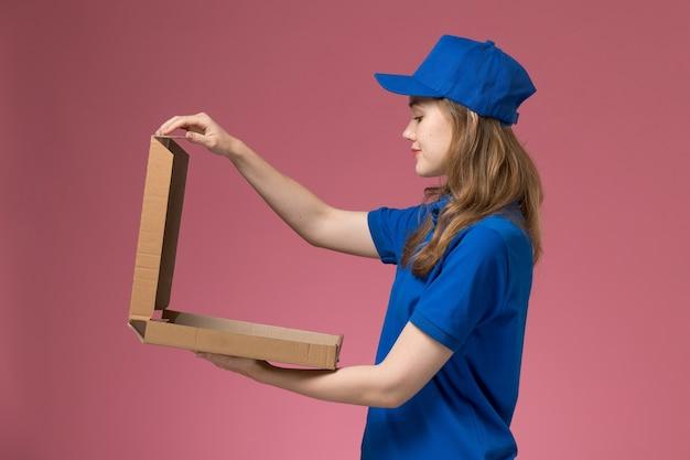 Vooraanzicht vrouwelijke koerier in blauw uniform met voedseldoos openen op roze bureau baan werknemer dienst uniform bedrijf