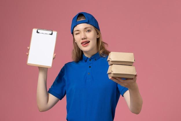 Vooraanzicht vrouwelijke koerier in blauwe uniforme cape die kleine pakketjes van het bezorgvoedsel en blocnote houdt die op de roze werknemer van de achtergrondbezorgdienst knipogen