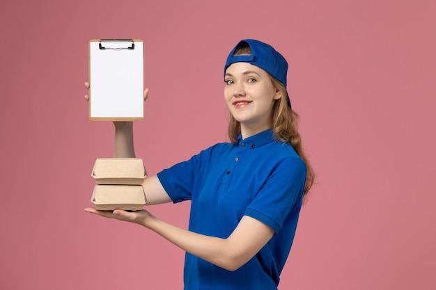 Vooraanzicht vrouwelijke koerier in blauwe uniforme cape die kleine pakketjes van het leveringsvoedsel en blocnote op het roze baanwerk van de achtergrondbezorgdienst houdt