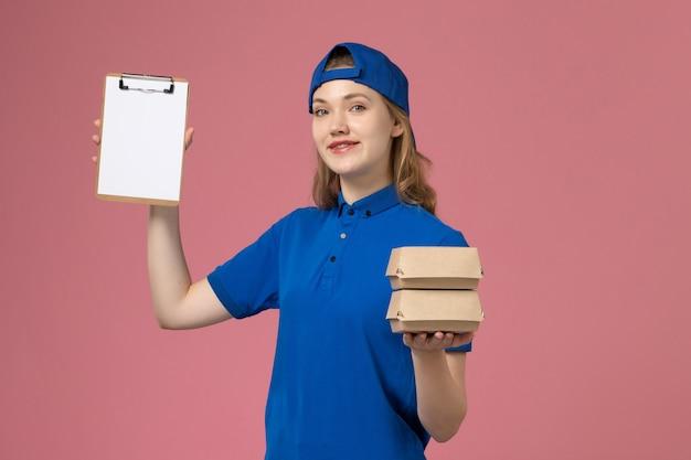 Vooraanzicht vrouwelijke koerier in blauwe uniforme cape die kleine pakketjes van het leveringsvoedsel en blocnote op roze achtergrondbezorgingsmedewerker houdt