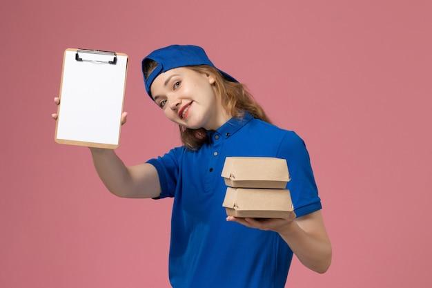 Vooraanzicht vrouwelijke koerier in blauwe uniforme cape die kleine pakketjes van het leveringsvoedsel en blocnote op roze achtergrondwerk van de de dienstmedewerker van de baanlevering houdt