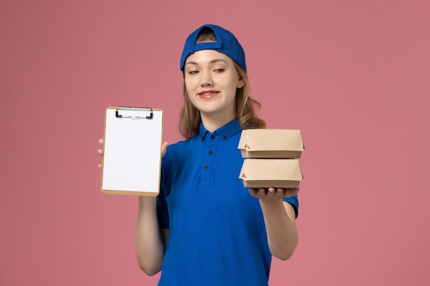 Vooraanzicht vrouwelijke koerier in blauwe uniforme cape die kleine pakketjes van het leveringsvoedsel en blocnote op roze werknemer van de achtergrondbezorgdienst houdt