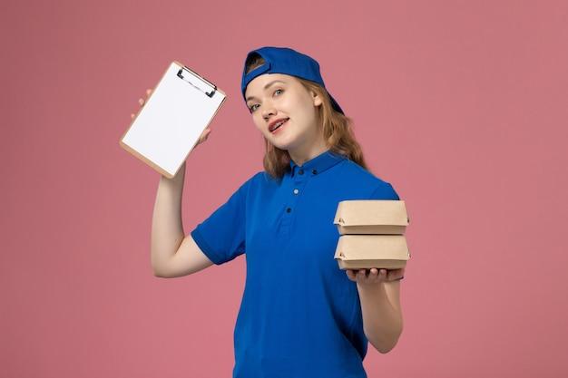 Vooraanzicht vrouwelijke koerier in blauwe uniforme cape die weinig voedselpakketten en blocnote op het roze werk van de achtergrondbezorgdienst houdt