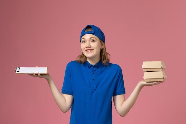 Vooraanzicht vrouwelijke koerier in blauwe uniforme cape die weinig voedselpakketten en blocnote op roze achtergrond het werkbaan van de bezorgdienst houdt