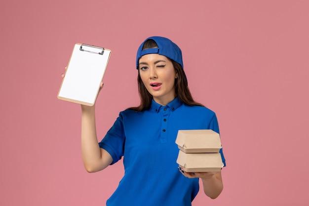 Vooraanzicht vrouwelijke koerier in blauwe uniforme cape met blocnote en kleine bezorgpakketten knipogen op lichtroze muur, levering servicemedewerker