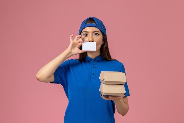 Vooraanzicht vrouwelijke koerier in blauwe uniforme cape met kaart en kleine bezorgpakketten op lichtroze muur, bezorgbaan van servicemedewerker