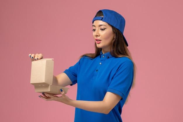 Vooraanzicht vrouwelijke koerier in blauwe uniforme cape met klein afleverpakket openen op roze muur, levering door werknemer