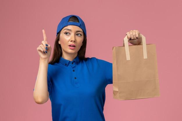 Vooraanzicht vrouwelijke koerier in blauwe uniforme cape met papieren afleverpakket op de lichtroze muur, servicemedewerker aan het leveren