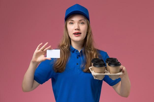 Vooraanzicht vrouwelijke koerier in blauwe uniforme holdingskaart en bruine bezorgingskoffiekopjes op lichtroze desk service uniforme bedrijfsmedewerker