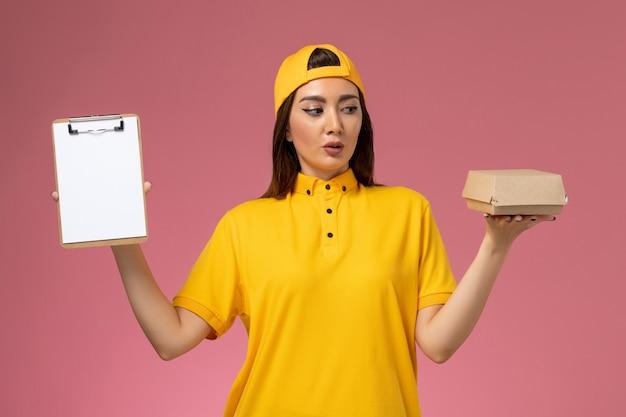 Vooraanzicht vrouwelijke koerier in geel uniform en cape die een klein pakket met voedsel en een blocnote vasthoudt op een lichtroze muurbediende uniforme bezorger