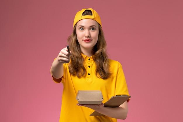 Vooraanzicht vrouwelijke koerier in geel uniform en cape die kleine voedselpakketpen en blocnote vasthoudt op het lichtroze muurbezorgingsuniform
