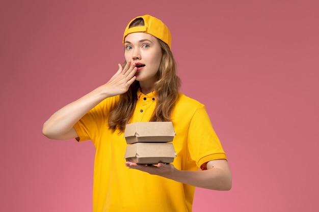 Vooraanzicht vrouwelijke koerier in geel uniform en cape die kleine voedselpakketten vasthoudt op de roze muur