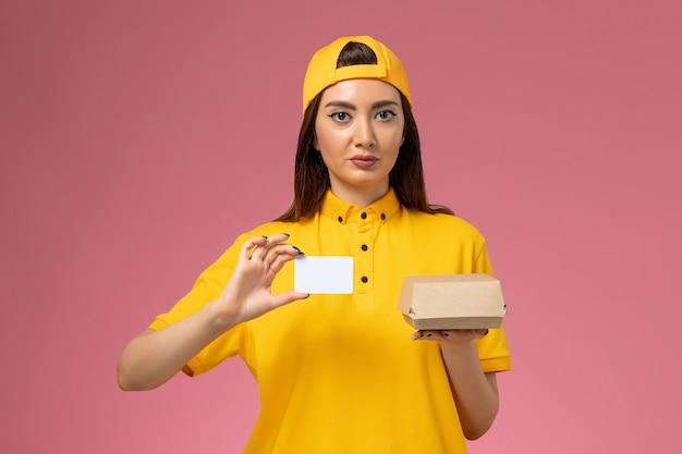 Vooraanzicht vrouwelijke koerier in geel uniform en cape die weinig voedselpakket en kaartje vasthoudt op lichtroze muurdienstuniform bezorgbedrijf werknemer baan