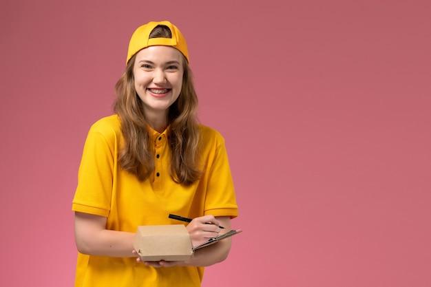 Vooraanzicht vrouwelijke koerier in geel uniform en cape die weinig voedselpakket voor bezorging en blocnote houdt die op een lichtroze uniform van de levering van de muurdienst schrijft