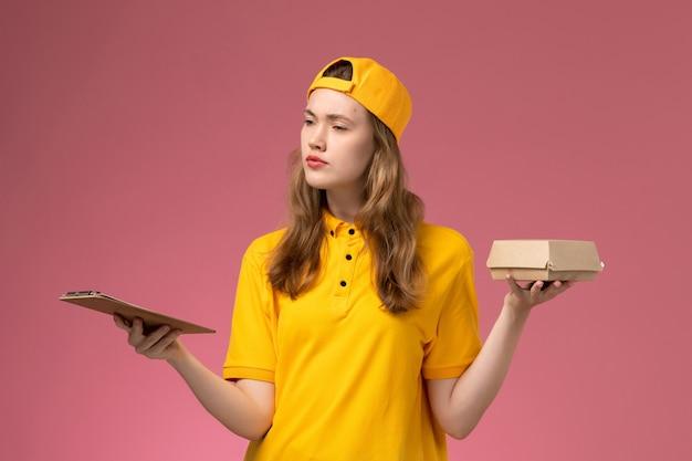 Vooraanzicht vrouwelijke koerier in geel uniform en cape die weinig voedselpakket voor bezorging en blocnote houdt en denkt aan een lichtroze uniform voor bezorging aan de muur