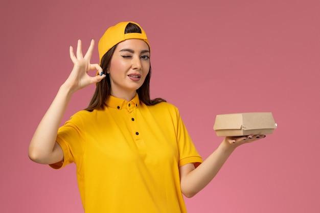 Vooraanzicht vrouwelijke koerier in geel uniform en cape die weinig voedselpakket voor bezorging op de roze muur houdt