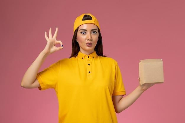Vooraanzicht vrouwelijke koerier in geel uniform en cape die weinig voedselpakket voor bezorging op lichtroze muurwerk van een uniform dienstverlenend bedrijf houdt