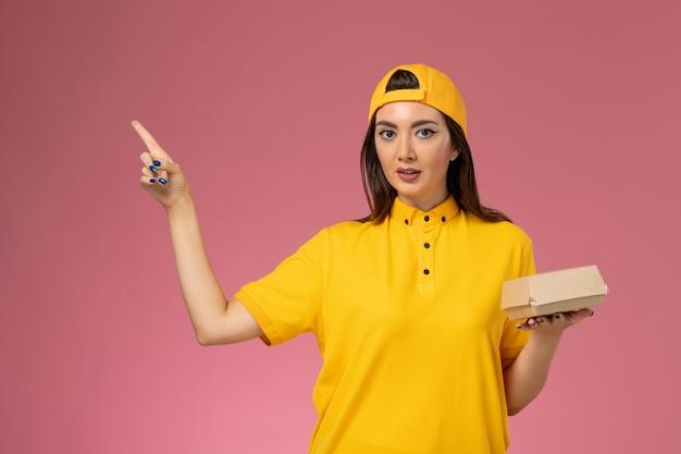 Vooraanzicht vrouwelijke koerier in geel uniform en cape die weinig voedselpakket voor bezorging op roze muuruniform meisjesservicebedrijf houdt