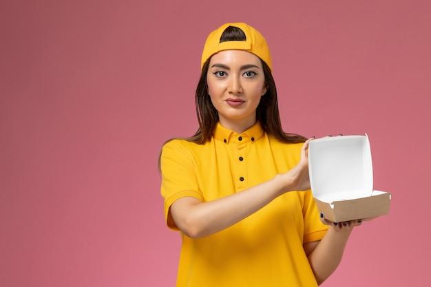 Vooraanzicht vrouwelijke koerier in geel uniform en cape die weinig voedselpakket voor bezorging vasthoudt en het opent op de roze werknemer van het uniforme dienstverlenende bedrijf