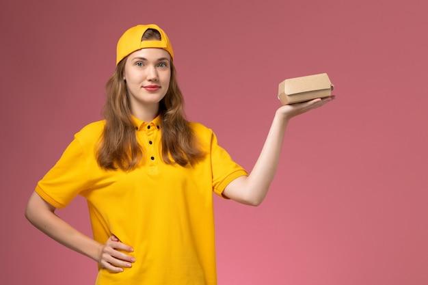 Vooraanzicht vrouwelijke koerier in geel uniform en cape met bezorgingsvoedselpakket op roze muurdienstbezorging uniform baanmeisje