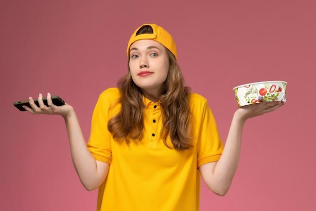 Vooraanzicht vrouwelijke koerier in geel uniform en cape met bezorgkom met telefoon op de roze muur