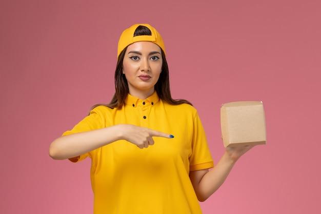 Vooraanzicht vrouwelijke koerier in geel uniform en cape met een klein pakket met voedsel voor bezorging op een lichtroze, uniform dienstverlenend bedrijf