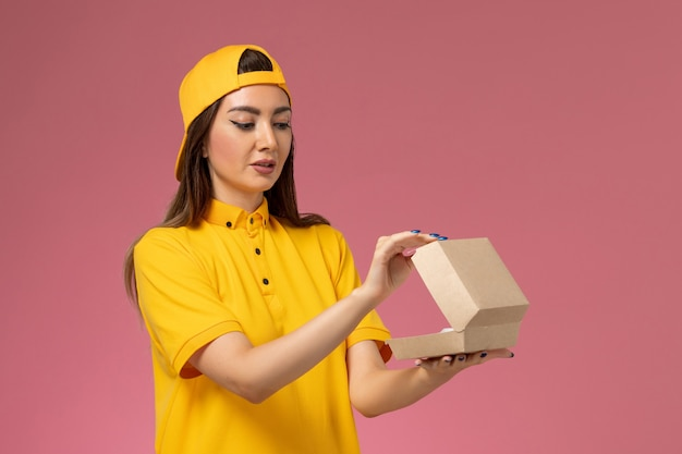 Vooraanzicht vrouwelijke koerier in geel uniform en cape met een klein pakket met voedsel voor bezorging, open het op roze muur uniform dienstverlenend bedrijf