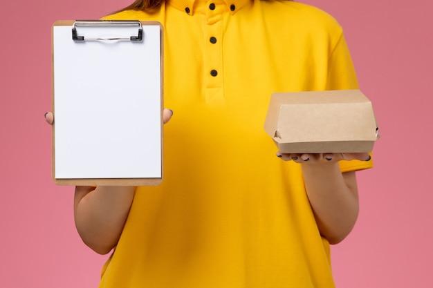 Vooraanzicht vrouwelijke koerier in geel uniform en cape met een klein voedselpakket en een blocnote op de lichtroze service-uniforme bezorgopdracht aan de muur