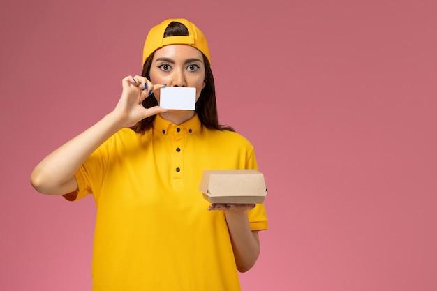 Vooraanzicht vrouwelijke koerier in geel uniform en cape met klein pakket met voedsel voor bezorging en kaart op lichtroze muur, dienstuniform bezorgbedrijf werkbaan