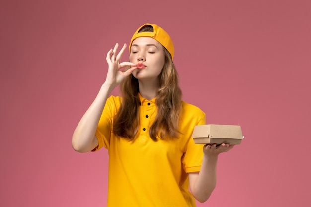 Vooraanzicht vrouwelijke koerier in geel uniform en cape met voedselpakket voor bezorging op de roze muur