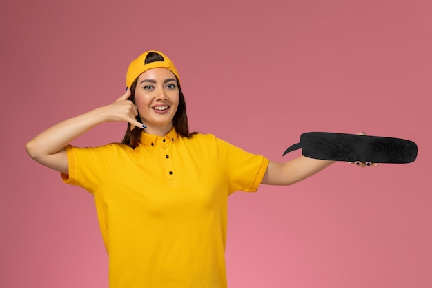 Vooraanzicht vrouwelijke koerier in geel uniform en cape met zwart bordje op de roze muur