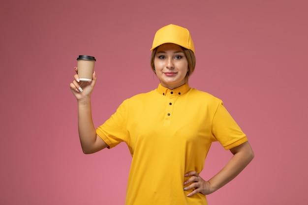 Vooraanzicht vrouwelijke koerier in gele uniform gele cape glimlachend bedrijf plastic bruine koffiekopje op roze bureau uniforme levering vrouwelijke kleur