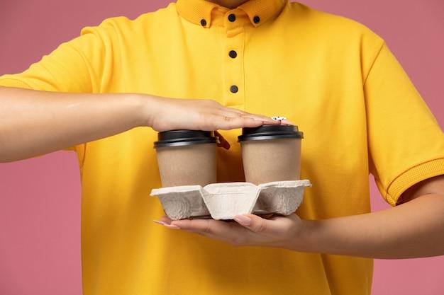 Vooraanzicht vrouwelijke koerier in gele uniform gele cape koffie houden op de roze achtergrond uniforme levering werk kleur