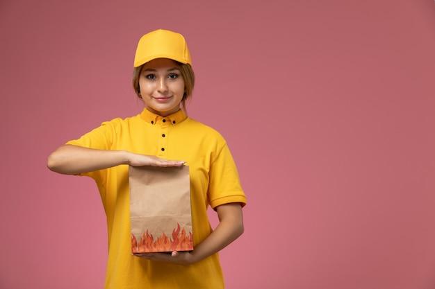 Vooraanzicht vrouwelijke koerier in gele uniform gele cape met voedselbezorgingspakket op de roze achtergrond uniforme levering werkbaan