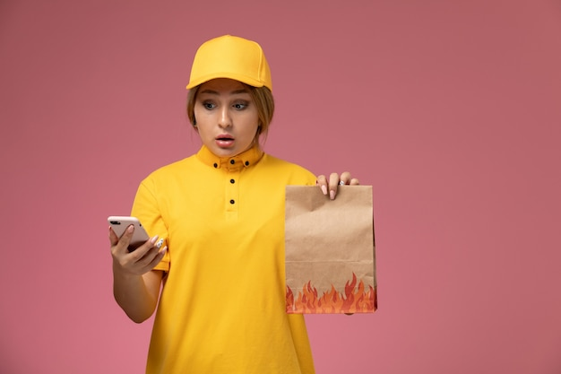 Vooraanzicht vrouwelijke koerier in gele uniform gele cape voedselpakket houden en met behulp van smartphone op roze achtergrond uniforme levering werk kleur baan