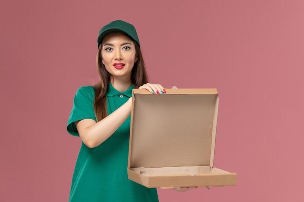 Vooraanzicht vrouwelijke koerier in groen uniform bedrijf en opening van lege voedseldoos op de roze muur dienst uniforme bezorger