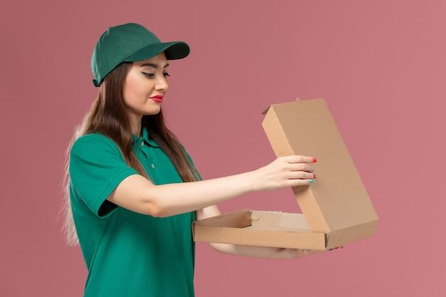 Vooraanzicht vrouwelijke koerier in groen uniform bedrijf en opening van lege voedseldoos op de roze muur job service uniforme levering