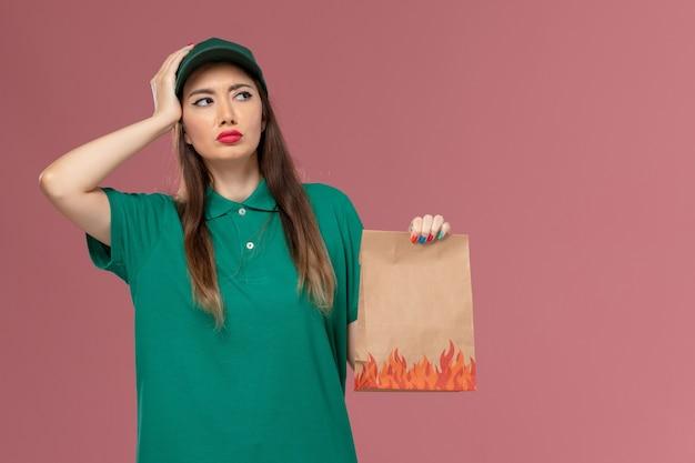 Vooraanzicht vrouwelijke koerier in groen uniform bedrijf papier voedselpakket denken aan roze muur service uniforme levering