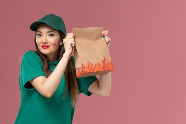 Vooraanzicht vrouwelijke koerier in groen uniform bedrijf papier voedselpakket glimlachend op roze muur service uniforme levering