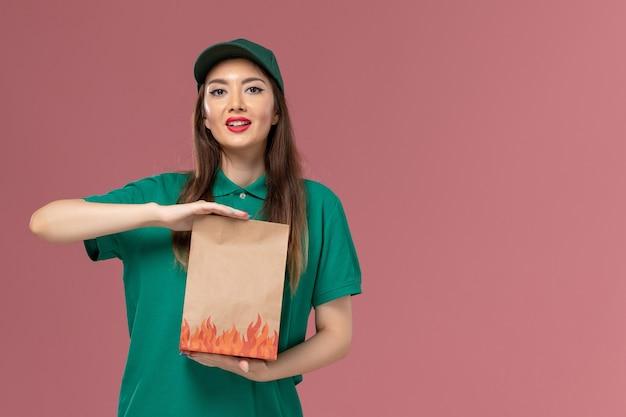 Vooraanzicht vrouwelijke koerier in groen uniform bedrijf papier voedselpakket op de roze muur service uniforme baan werknemer levering