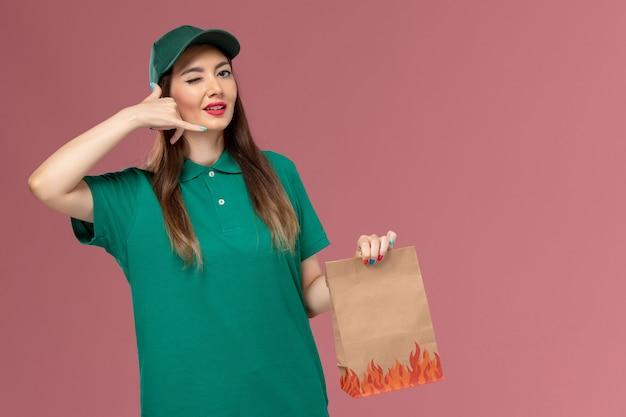 Vooraanzicht vrouwelijke koerier in groen uniform bedrijf papier voedselpakket op roze muur service uniform leveringswerk