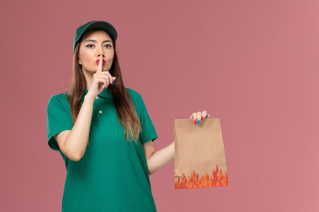 Vooraanzicht vrouwelijke koerier in groen uniform bedrijf papier voedselpakket op roze muur service uniforme bezorger