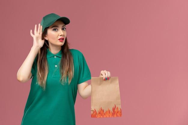 Vooraanzicht vrouwelijke koerier in groen uniform bedrijf papier voedselpakket proberen te horen op roze muur service uniforme levering