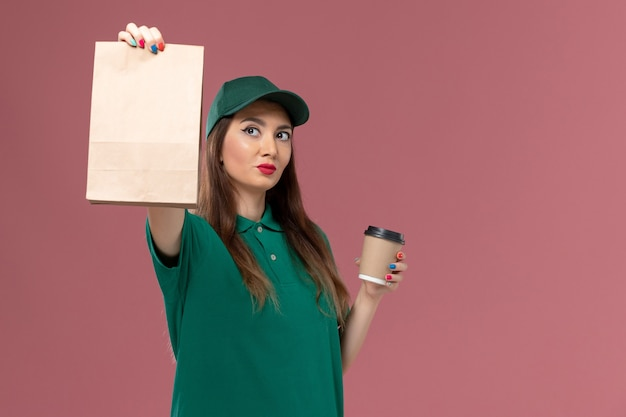 Vooraanzicht vrouwelijke koerier in groen uniform en cape bedrijf levering koffiekopje en voedselpakket op roze muur bedrijf dienst baan uniforme bezorger vrouwelijk werk