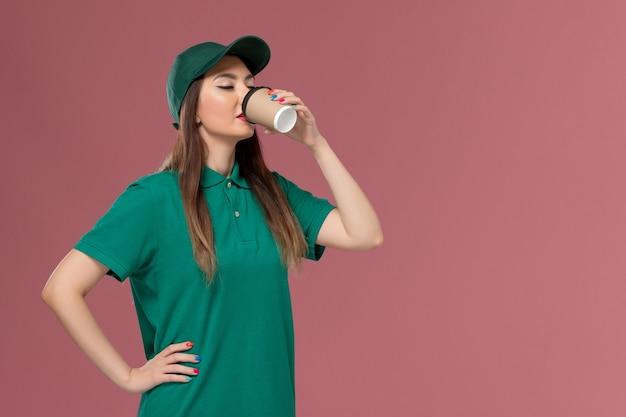 Vooraanzicht vrouwelijke koerier in groen uniform en cape die koffie drinkt op de lichtroze muurdienstbaan uniforme levering