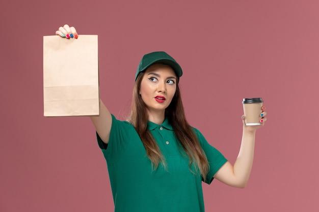 Vooraanzicht vrouwelijke koerier in groen uniform en cape met bezorging koffiekopje en voedselpakket op de roze muur bedrijfsservice baan uniforme levering