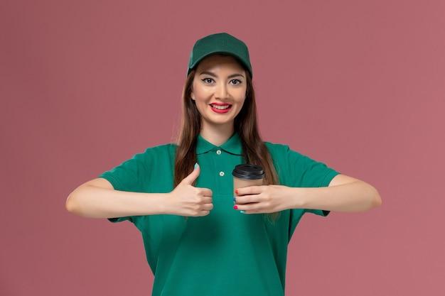 Vooraanzicht vrouwelijke koerier in groen uniform en cape met bezorging koffiekopje op de lichtroze muur service job uniforme levering