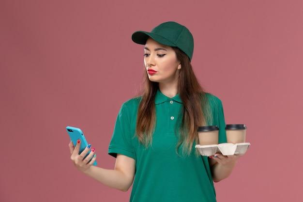 Vooraanzicht vrouwelijke koerier in groen uniform en cape met bezorging koffiekopjes en telefoon op roze muur service job uniforme levering