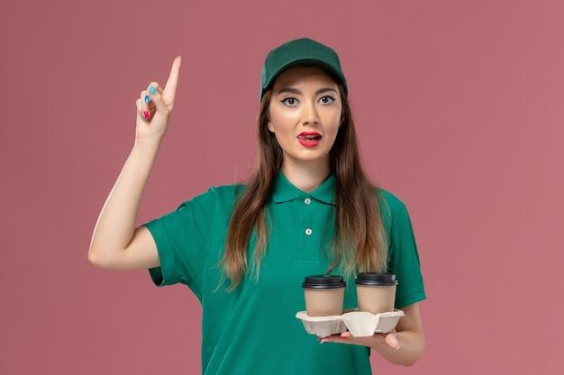 Vooraanzicht vrouwelijke koerier in groen uniform en cape met bezorging koffiekopjes met opgeheven vinger op roze muur bedrijfsservice baan uniforme levering