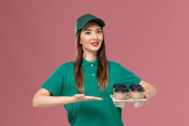 Vooraanzicht vrouwelijke koerier in groen uniform en cape met bezorging koffiekopjes op lichtroze muur service uniforme bezorgopdracht